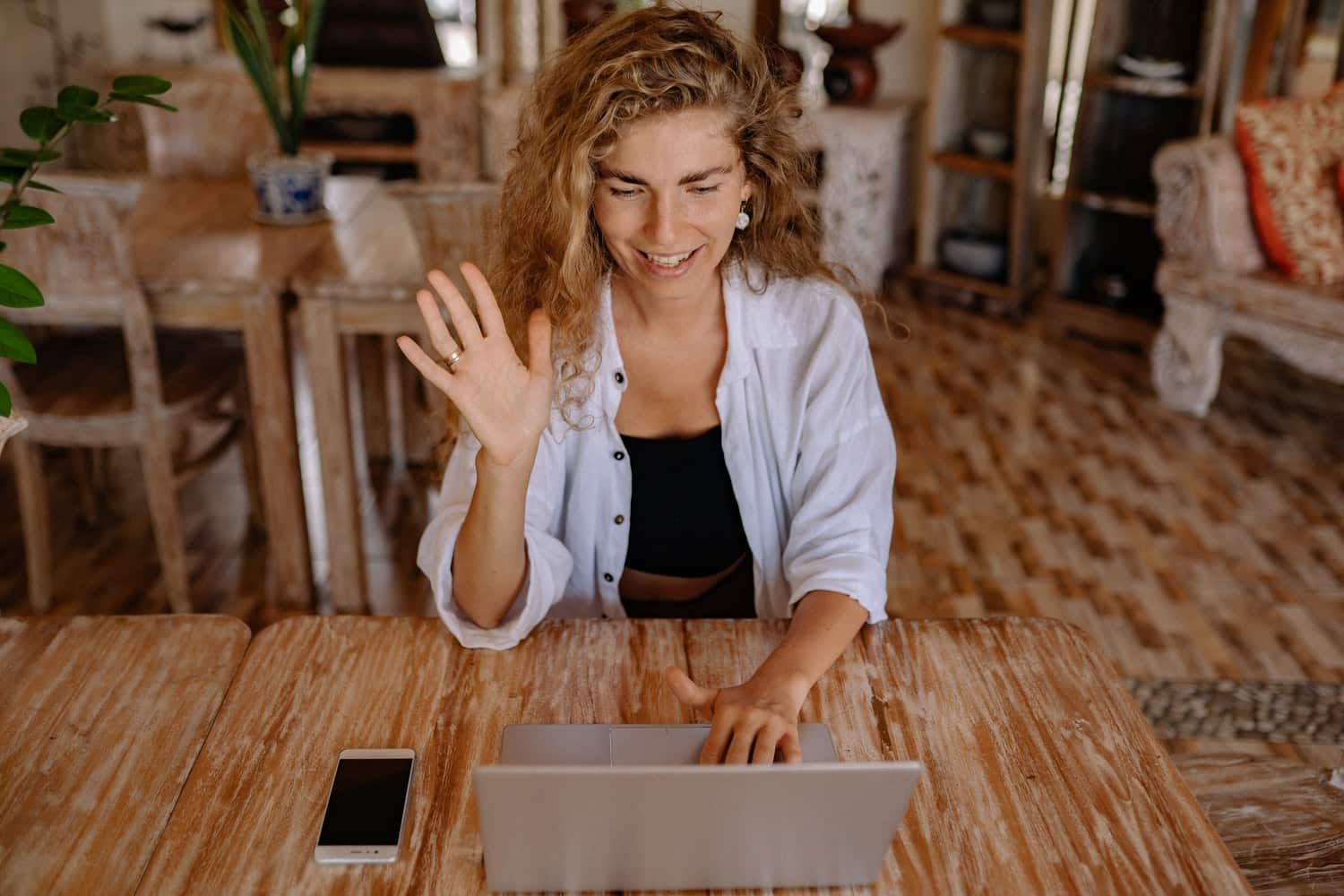 Woman smiles and waves during an online meeting
